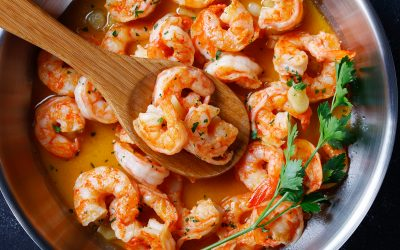 Italian shrimp scampi with garlic butter sauce served with lemon and parsley, on a skillet on concrete background, top view, horizontal orientation, close-up